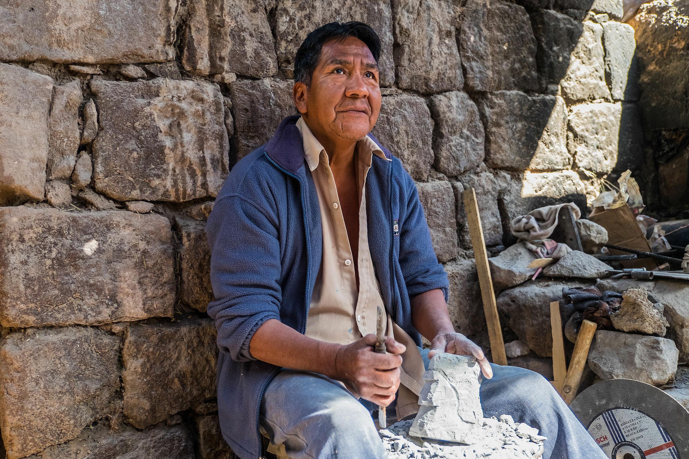 Sculptor of Andea rock between walls of adobe...